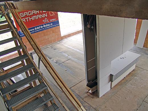Ein Blick vom Obergeschoß ins Untergeschoß. Man sieht die offene Seite des Pfeilers, welcher einerseits die Installationen fürs Obergeschoß aufnimmt und andererseits als 'optischer' Kaminabzug gedacht ist.