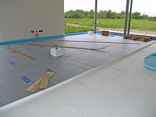 Teilweise wurden im Untergeschoß bereits die Auflagen für die Bodenheizung auf den Styroporplatten verlegt. Auch hier sieht man am Bild die beiden Bodensteckdosen-Vorbereitungen.