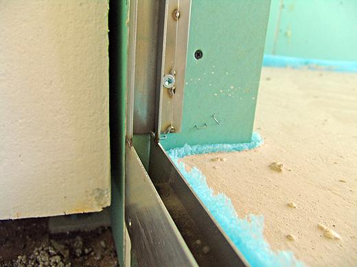 Im Rohbau wurde das Nirosta-Profil bereits an der Betondecke und der Rigipswand fixiert, damit die Glaswand nachher nicht wackelt. Die Wandleibung (Bildmitte oben) wurde mit einer zweiten Rigipsplatte beplankt um das Profil plan in die Wand zu versenken. Auf der Duschseite wurden die Wandfliesen bis über das Profil gezogen und mit einer Alukantleiste abgeschlossen.