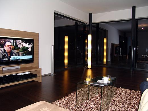 Das Heimkino im Wohnzimmer steht natürlich schon. Die Stehlampe in der Ecke spiegelt sich in der Fixverglasung - dadurch erleuchten diese 27 Watt das ganze Wohnzimmer. Auch hinter dem TV gibt es eine indirekte Beleuchtung.