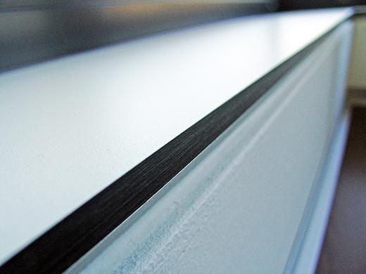 Aufbau: Mauer > Schattenfuge mit Aluminiumleiste > schwarze Front > weiße Oberseite. Die Aluminiumleiste sieht man nicht auf den ersten Blick - weil die Fensterbank auf 20 cm über dem Boden sitzt.