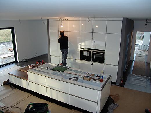 Grifflose Hochglanz-Glasfronten in Weiß mit Siemens Küchengeräten und einer schwarzen, 8cm starken Granitarbeitsplatte. Das ist unser ganz persönlicher Traum.