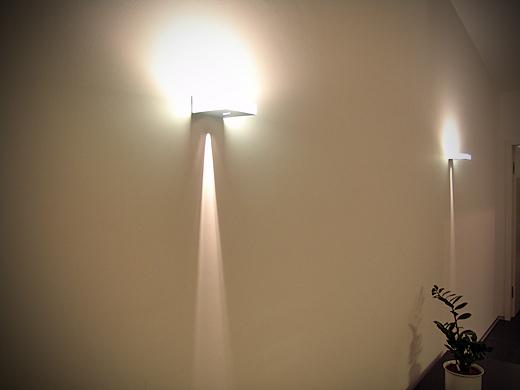 Die Wandleuchten sind mit 40 Watt Halogenlampen bestückt und strahlen durch einen schmalen Schlitz nach unten. Der Großteil des Lichtes geht nach oben. Die Leuchten sind schlicht und elegant zugleich.
