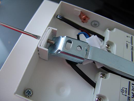 Anschließend den Montagewinkel lösen - dieser wird dann mit zwei Schrauben an der Decke montiert und mit dem Stift links und rechts wieder fixiert.