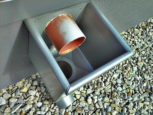 Das Bürodach hat keinen direkten Abfluß und wird über zwei solche Entwässerungen auf das Mitteldach entwässert. Dort fließt das Wasser dann zu dem ganz oben abgebildeten Laubfangkörben.