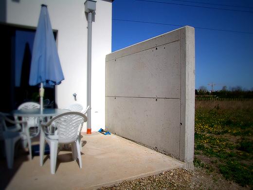 """Die Sichtbetonwand haben wir bis jetzt noch nicht viel """"beschrieben"""". Die Wand trennt die Ostterrasse vom Nachbargrundstück. Auch weil die Terrassentür sonst zu nah am Nachbarn gewesen wäre. Diese Betonwand ist ein super Wind- und Sonnenschutz und auf der Ostterrasse ist es am Vormittag am angenehmsten."""