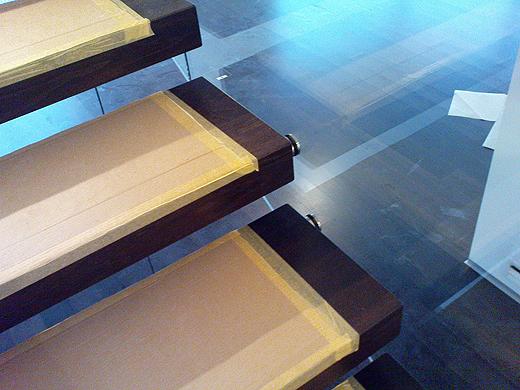 Die Glasbrüstung wurde mit einem Abstandhalter direkt an die Stufen geschraubt. Vorerst haben wir das Glasgeländer ohne Niro-Handlauf bestellt. Sollte es sich verbiegen (es besteht aus zwei Teilen), dann können wir immer noch eine Niro-Profil oben draufstecken - wie vom Stiegenbauer vorgeschlagen.