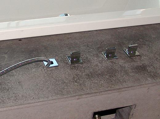 Der integrierte Ab- und Überlauf muss laut Installateur noch eingestellt werden. Die Revisionsöffnung am Sockel wird später mit einer gebürsteten Aluminiumplatte verschlossen.