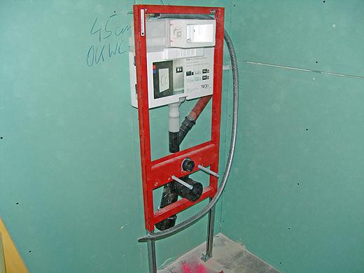 """Der Unterputzspülkasten und die WC Tragekonstruktion stehen bereits. Am Bild kann man auch die Abzweigung im Wasserfallrohr sehen. Dort wird (wenn nicht gerade gespült wird) die """"verbrauchte"""" Luft direkt von der Toilettenschüssel abgesaugt."""